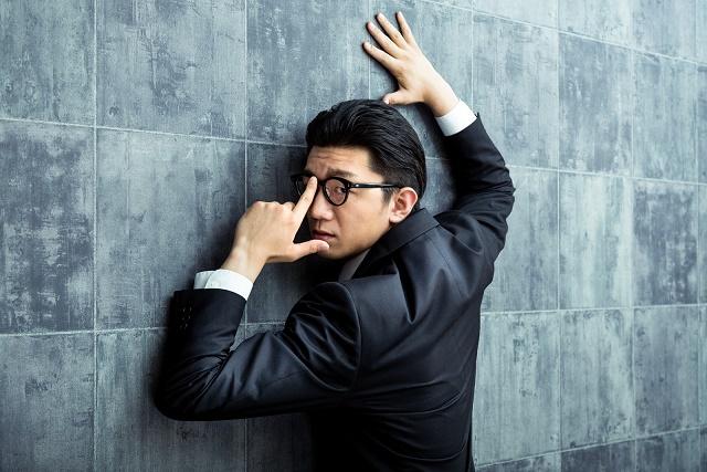 メガネを上げる男