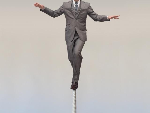 綱渡りするスーツの男